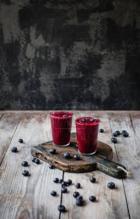 Delicious berry smoothie in glasses on rustic wooden board