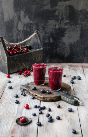 Organic berry smoothie in glasses on wooden background