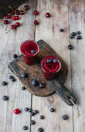 Summer berries and delicious detox smoothie on rustic wooden board