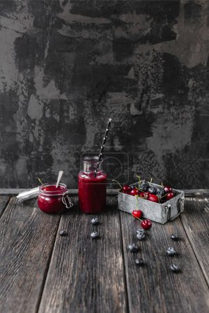 Ripe berries and delicious detox smoothie on rustic wooden board