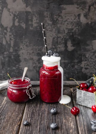 Delicious detox smoothie in bottle and jar on rustic wooden board