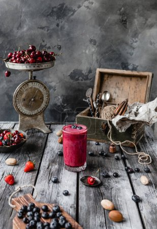 Delicious detox smoothie on rustic wooden board with ripe berries