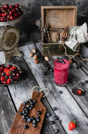 Fresh healthy smoothie in glass on rustic table with summer berries