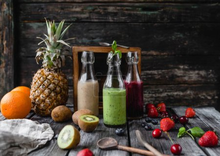 Photo for Organic fruit smoothies in glass bottles on wooden background with assorted fruits - Royalty Free Image