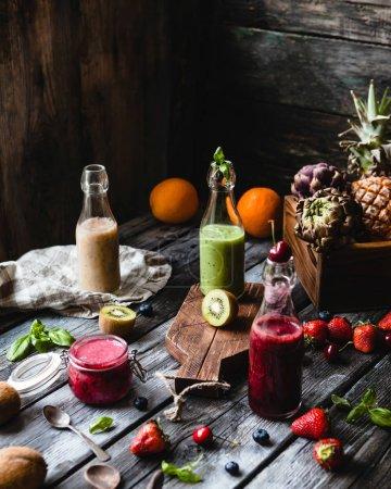 Photo pour Smoothies frais et sains en bouteilles de verre sur table rustique avec des fruits variés - image libre de droit