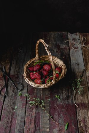 Photo for Ripe tasty strawberries in straw basket on wooden table - Royalty Free Image