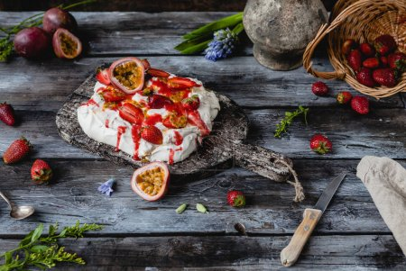 Photo for Tasty strawberry and passion fruit meringue cake on wooden table - Royalty Free Image