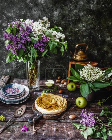 Photo for Delicious apple pie and lilac flowers on wooden table - Royalty Free Image