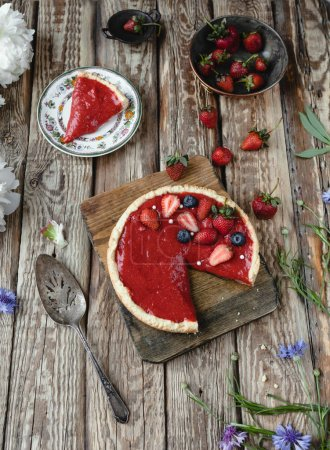 delicious red strawberry pie with berries on wooden table