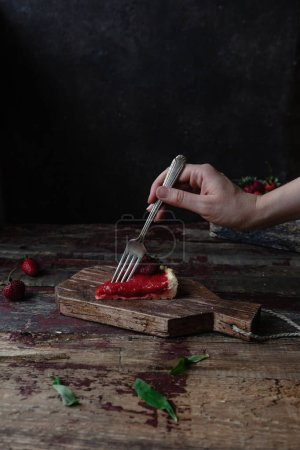 Photo for Cropped image of woman taking piece of strawberry pie with fork - Royalty Free Image