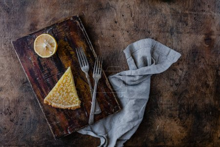 Photo for Elevated view of piece of tasty lemon pie on cutting board - Royalty Free Image