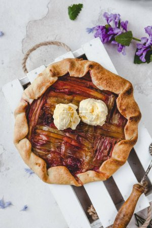 Photo for Top view of yummy rhubarb pie with cream on table - Royalty Free Image