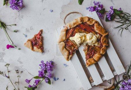 Photo pour Vue de tarte rhubarbe délicieux sur la table avec des fleurs violettes - image libre de droit