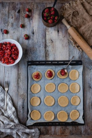 Photo for Top view of preparation of yummy cookies with strawberries on tray - Royalty Free Image
