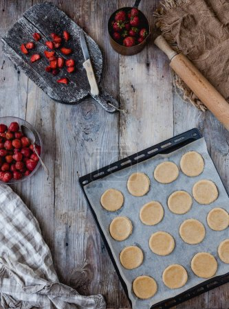 Photo for Elevated view of preparation of cookies with strawberries on tray - Royalty Free Image