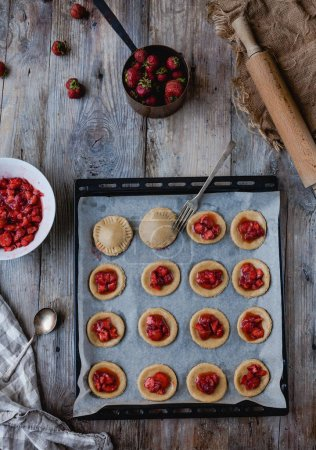 Photo for Top view of unprocessed cookies with strawberries and fork on tray - Royalty Free Image