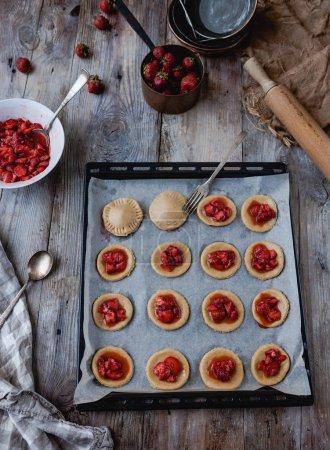 Photo pour Vue d'angle élevé de préparation des cookies avec des fraises sur plateau - image libre de droit