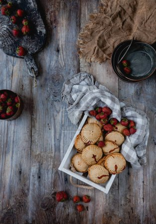 Photo for Elevated view of tasty cookies with strawberries in tray on wooden table - Royalty Free Image