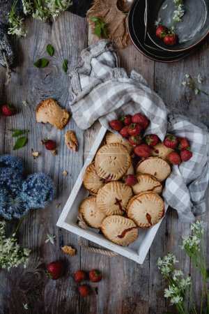 Photo for Top view of tasty cookies with strawberries in tray on table - Royalty Free Image