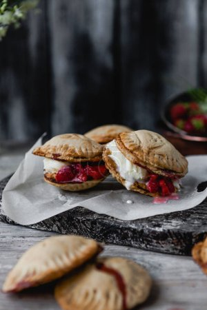 Photo for Selective focus of tasty cookies with strawberries and cream on wooden table - Royalty Free Image
