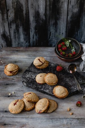 Photo for High angle view of tasty cookies with strawberries on wooden table - Royalty Free Image