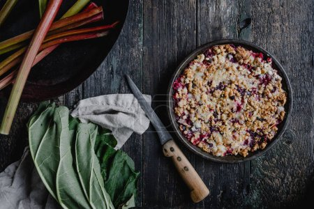 elevated view of yummy pie with berries and rhubarb on wooden table