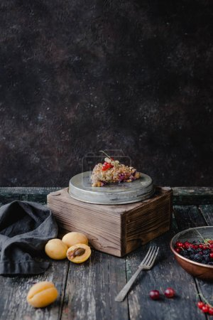 Photo for Piece of tasty pie with berries on stands on table - Royalty Free Image