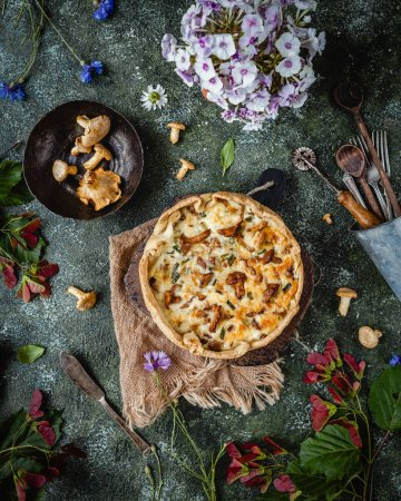 top view of appetizing quiche with mushrooms and potted flowers on wooden table