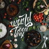 Vue des moules cuites de dessus avec des coquilles servis dans la poêle avec des tomates, herbes et vin sur table en bois, lettrage de journée alimentaire mondiale
