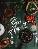 Vue des moules cuites de dessus avec des coquilles servis dans la poêle avec des tomates, herbes et vin sur table en bois, bon appetit lettrage