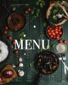Vue des moules cuites de dessus avec des coquilles servis dans la poêle avec des tomates, herbes et vin sur table en bois, lettrage de menu