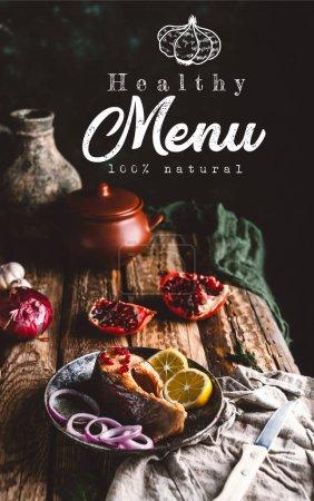 Photo pour Steak de saumon cuit au four avec citron et oignon dans une assiette avec grenade sur une table en bois, lettrage de menu sain - image libre de droit
