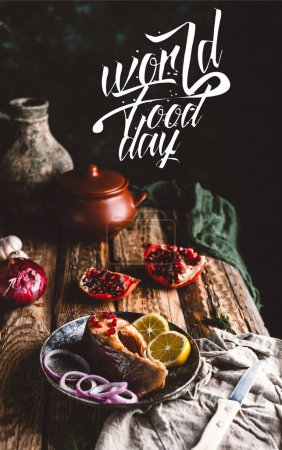 Photo for Baked salmon steak with lemon and onion on plate with pomegranate on wooden table, world food day lettering - Royalty Free Image