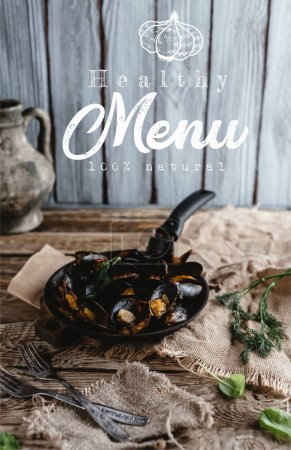gourmet fried mussels with shells on frying pan and forks on table, healthy menu lettering