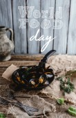 gourmet fried mussels with shells on frying pan and forks on table, world food day lettering