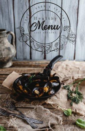 Foto de Gourmet frito mejillones con conchas en sartén y tenedores de mesa, Letras de menú saludable - Imagen libre de derechos