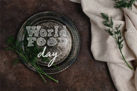 top view of vintage plate with fennel and tablecloth on dark surface, world food day lettering