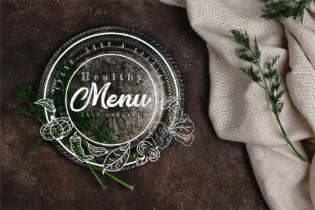 top view of vintage plate with fennel and tablecloth on dark surface, menu lettering