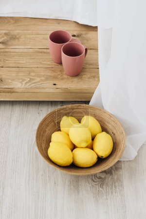 Photo for Pile of fresh lemons in wooden bowl - Royalty Free Image