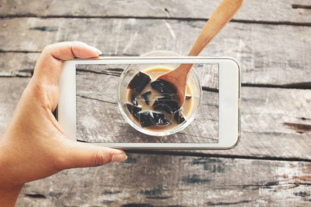 Taking a photo of coffee jelly with smart phones on hand