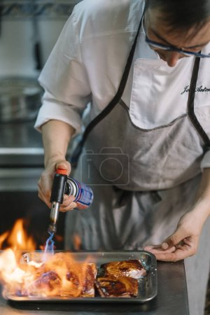 Chef cooking preparing food with fire torch.