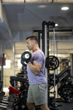 Photo for Strong man training in gym, train the arms. - Royalty Free Image
