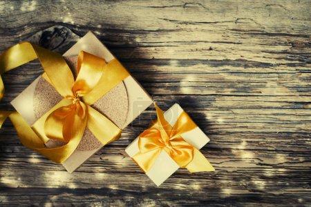 Photo pour Vue de dessus des boîtes à cadeaux avec rubans de satin sur la table en bois - image libre de droit