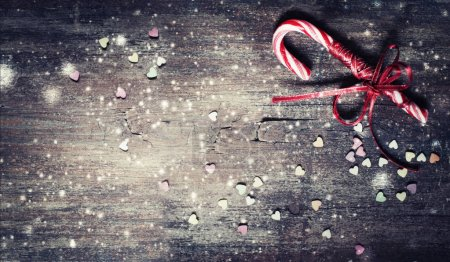 Photo for Christmas Candy Cane with Red Bow Isolated on wooden Background - Royalty Free Image