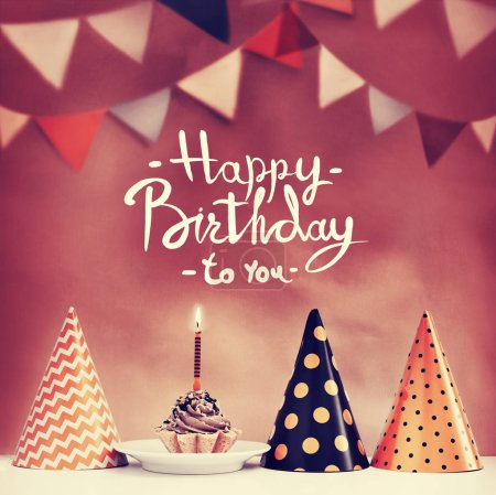 Photo for Birthday cake with candle and cone hats in vintage style, copy space - Royalty Free Image