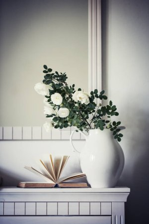 Photo for Branches of fresh roses in vase in room with open book - Royalty Free Image