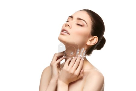 Photo for Beautiful young woman applying moisturizing skin cream on neck. studio beauty shot on white background. copy space - Royalty Free Image