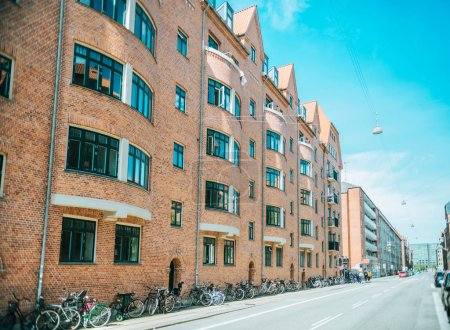 COPENHAGEN, DENMARK - MAY 5, 2018: urban scene with empty city street with parked bicycles and buildings in copenhagen, denmark
