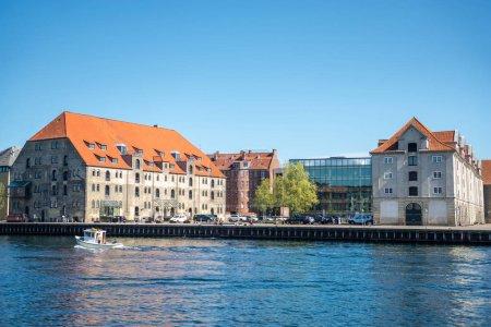COPENHAGEN, DENMARK - MAY 5, 2018: urban scene with city river and colorful buildings in copenhagen, denmark