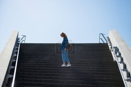 side view of woman standing on steps with blue sky on background in copenhagen, denmark